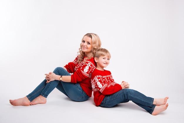 Matka i jej dziecko siedzą tyłem do siebie, uśmiechając się i patrząc