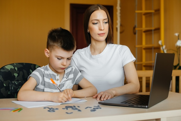 Matka i jej dziecko uczą się na odległość w domu przed komputerem