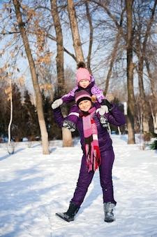 Matka i jej mała córka cieszy się pięknego zima dzień