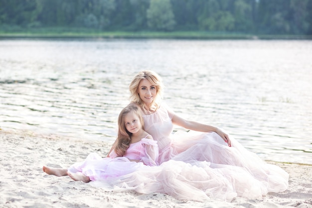Matka i jej mała dziewczynka, podziwiając widok na jezioro i relaksując się na plaży w słoneczny dzień w pięknych sukienkach. rodzinny styl życia i pojęcie miłości rodzinnej. szczęśliwa rodzina cieszy się słonecznego dzień na plaży.