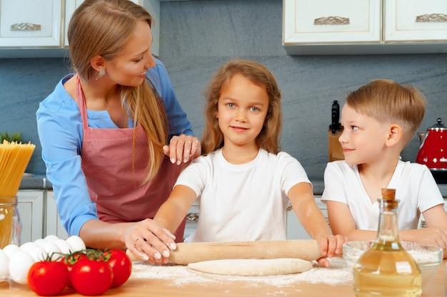 Matka i jej małe dzieci, chłopiec i dziewczynka, pomagając jej przygotować ciasto
