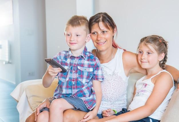 Matka i jej synowie oglądają telewizję siedząc na kanapie w domu. szczęśliwa mama i jej synowie na tylnej kanapie z pilotem do telewizora