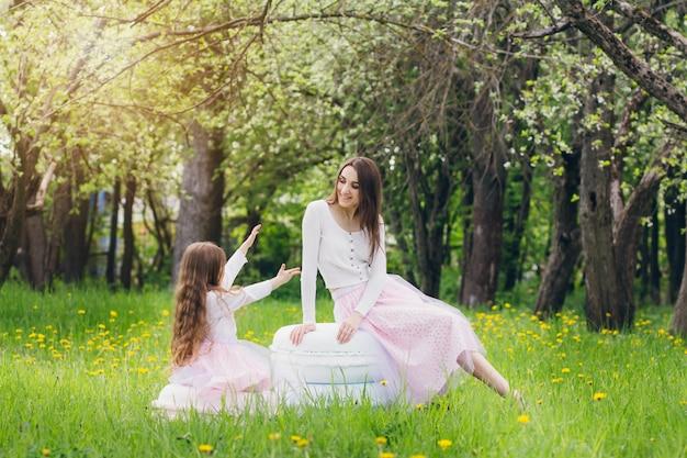Matka i mała córka chodzą wiosną kwitnącego jabłka