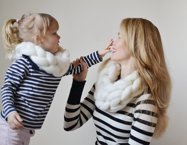 Matka i mała córka w kapeluszach i szaliku na białym tle, rodzinny spojrzenie