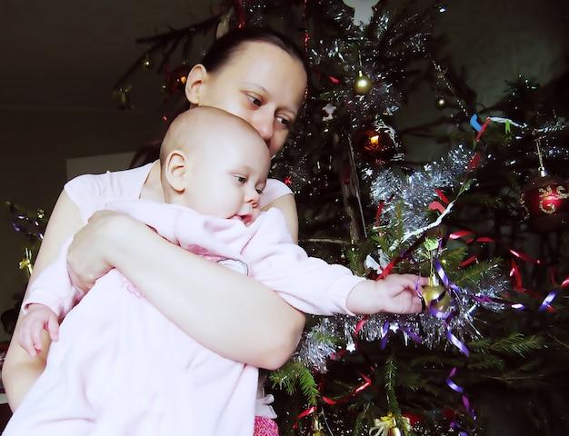 Matka i małe dziecko patrzą na dekorację choinki cristmas