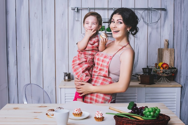 Matka i małe dziecko w kuchni w domu z fartuchami