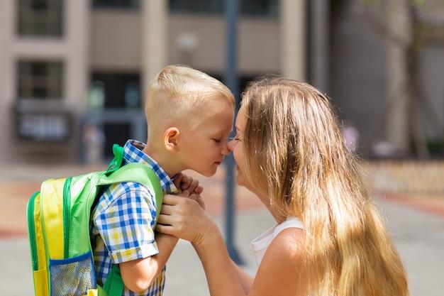 Matka i mały syn dotykając nosa przed szkołą