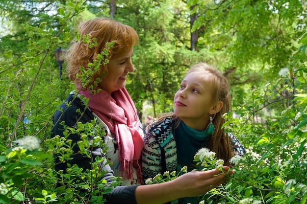 Matka i nastoletnia córka komunikują się i podziwiają kwitnące krzewy w parku
