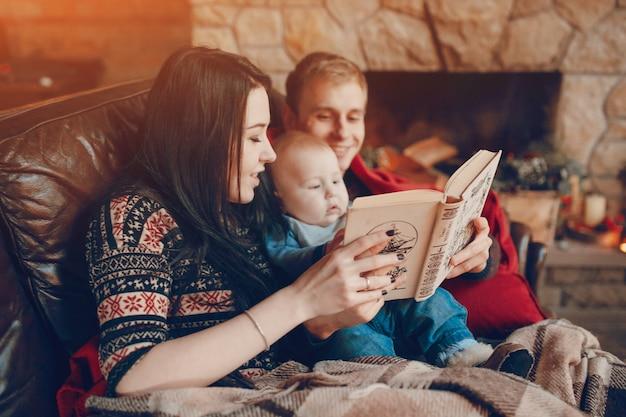Matka i ojciec czyta książkę z dzieckiem w środku