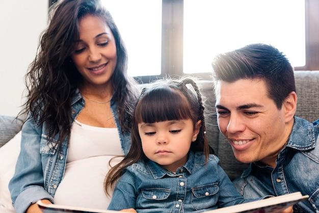 Matka i ojciec czytają książkę córce w domu.