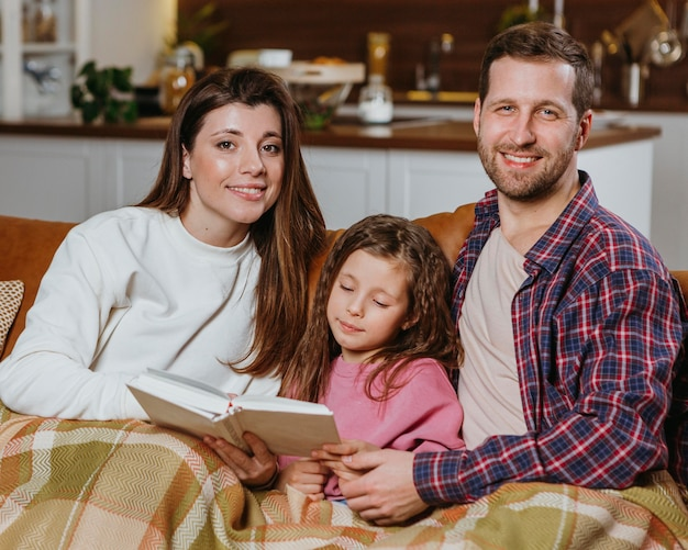 Matka i ojciec, czytanie książki w domu z córką