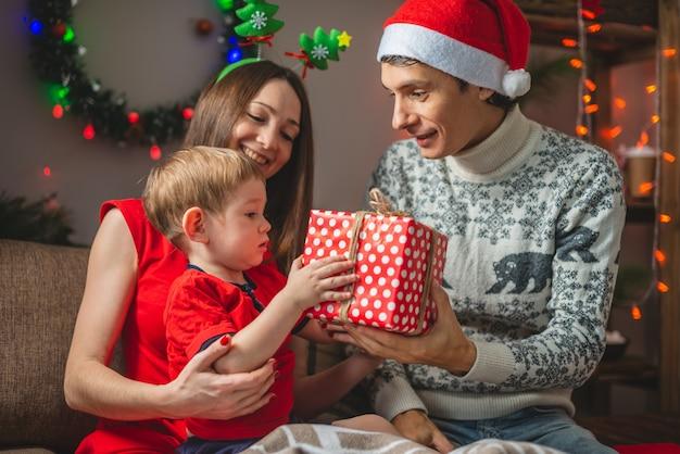 Matka i ojciec dają synowi prezent w czerwonym pudełku