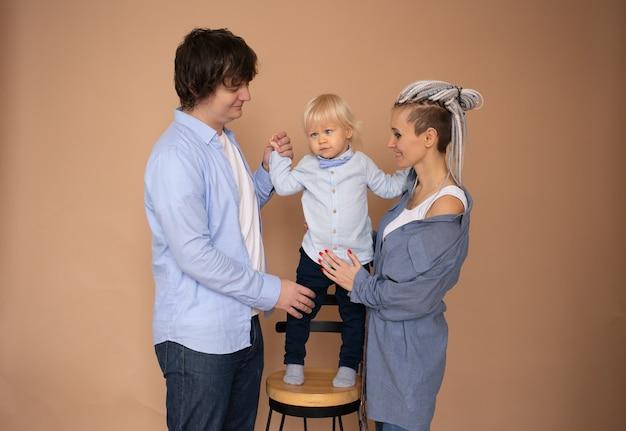 Matka i ojciec i synek na białym tle na beżowej ścianie