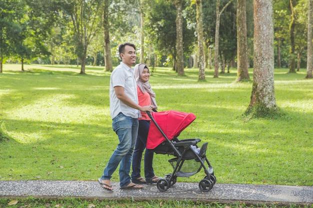 Matka i ojciec pchanie wózka dziecięcego w parku