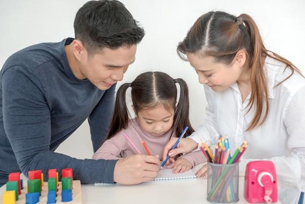 Matka i ojciec pomagają córce odrabiać lekcje w salonie