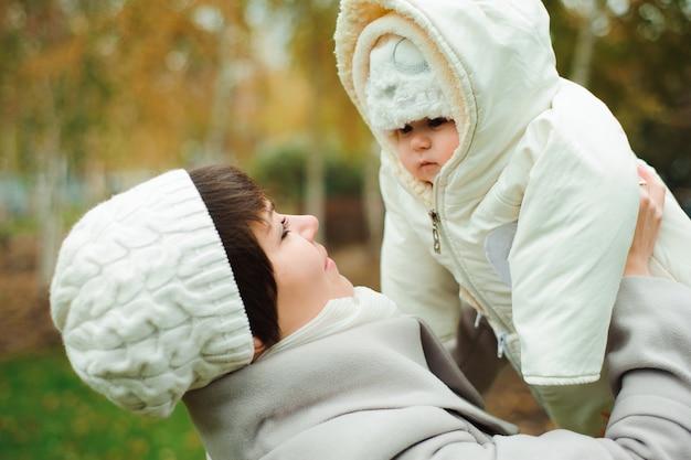 Matka i ojciec z dzieckiem ubrane w ciepłe ubrania, chodzenie w słoneczny dzień na zewnątrz. szczęśliwa rodzina spędza czas razem.