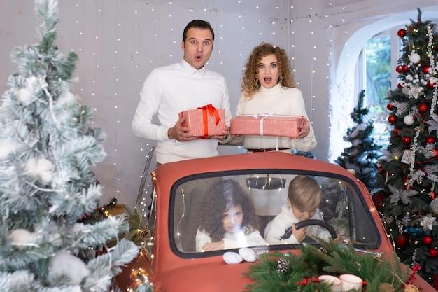 Matka i ojciec z pudełkami z prezentami w dłoniach i obok są dzieci w czerwonym samochodzie w pobliżu choinek.