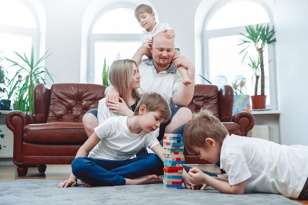 Matka i ojciec z trzema chłopcami. szczęśliwa i kochająca rodzina gra w grę jenga w domu i dobrze się bawi.