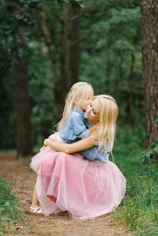 Matka i pięcioletnia córka w identycznych różowych tiulowych spódnicach i niebieskich dżinsowych koszulach spacerują po parku lub w lesie. córka przytula swoją matkę. dzień matki