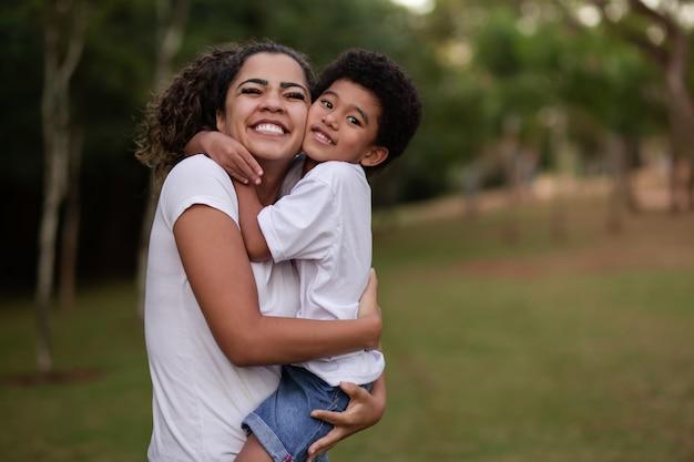 Matka i syn afro w parku uśmiechający się do kamery