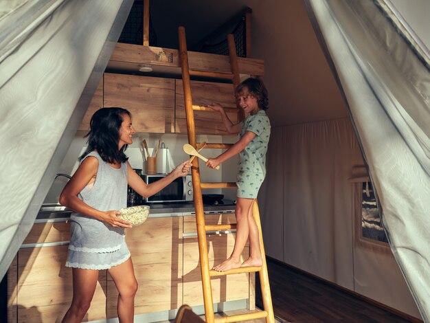 Matka i syn bawią się drewnianymi przyborami kuchennymi, jakby były mieczami w domu