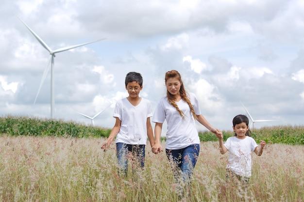 Matka i syn bawią się w polu z ogromną turbiną wiatrową w tle