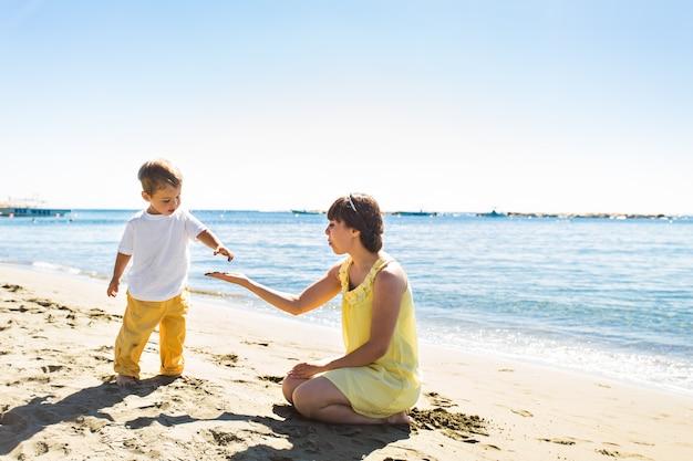 Matka i syn bawić się na lato tropikalnej plaży