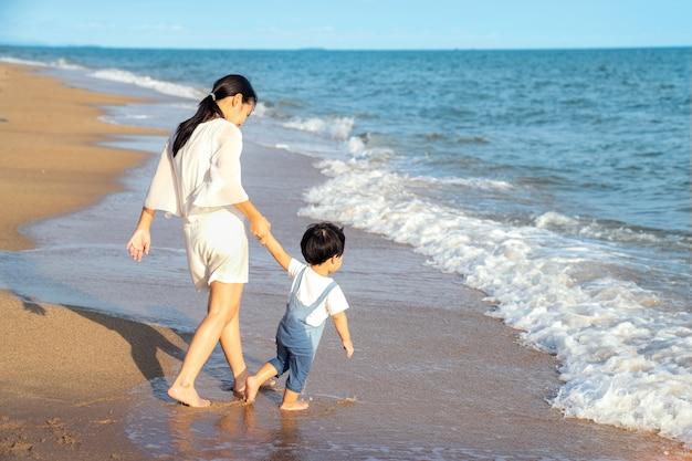 Matka i syn chodzić po plaży