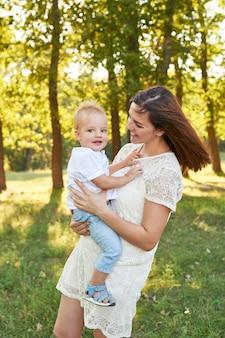 Matka i syn chodzić w parku w lecie o zachodzie słońca