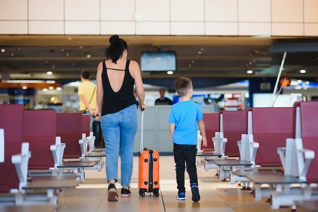 Matka i syn czekają na wejście na pokład przy bramce odlotów nowoczesnego terminalu międzynarodowego.