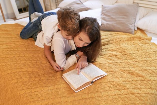 Matka i syn czytają książkę, leżąc na łóżku w domu