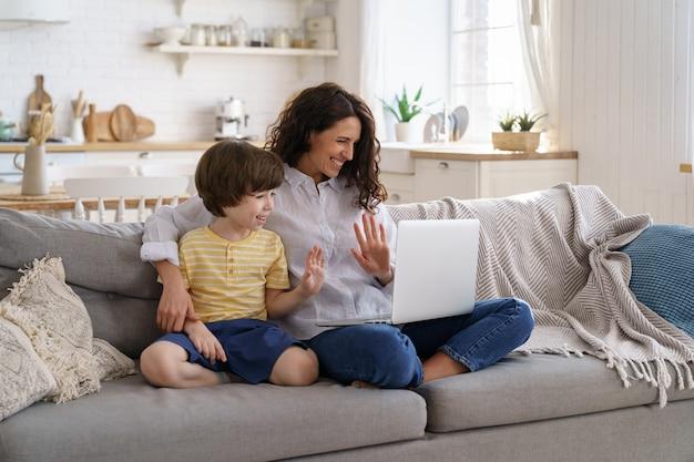 Matka i syn dziecko patrząc na laptopa z kamerą internetową do połączenia wideo w domu. rodzina, koncepcja blokady.
