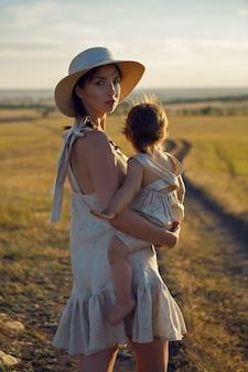 Matka i syn idzie na pole o zachodzie słońca w słomkowym kapeluszu