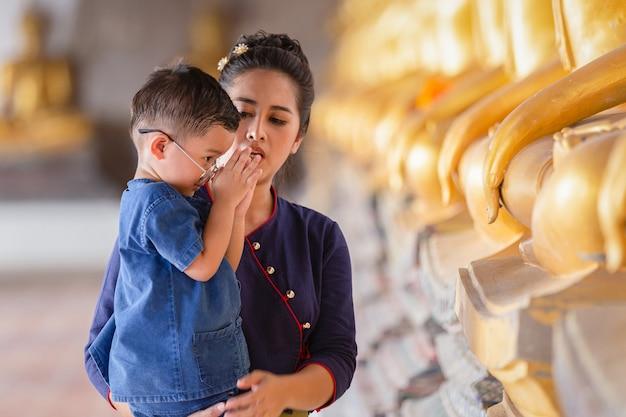 Matka i syn modląc się z szacunkiem posąg buddy w świątyni wat phutthai sawan, ayutthaya, tajlandia. koncepcja kultury tajskiej