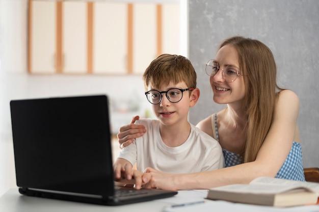 Matka i syn odrabiają lekcje na komputerze. siostra pomaga bratu w lekcjach. nauczyciel wyjaśnia dziecku temat.