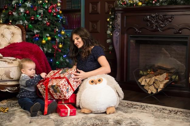 Matka i syn otwierają prezenty świąteczne na dywanie w pobliżu choinki i kominka.