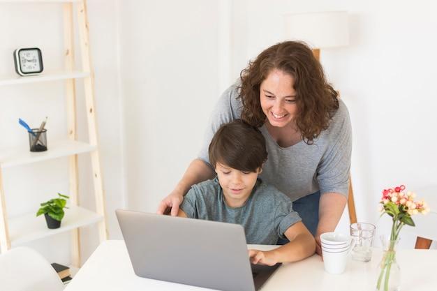 Matka i syn patrzeje na laptopie