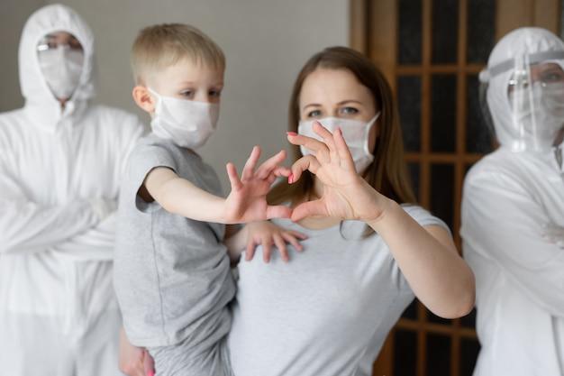 Matka i syn pokazują znak serca rękami na tle pracowników chorób zakaźnych w białych kombinezonach ochronnych podczas epidemii koronawirusa. covid-19