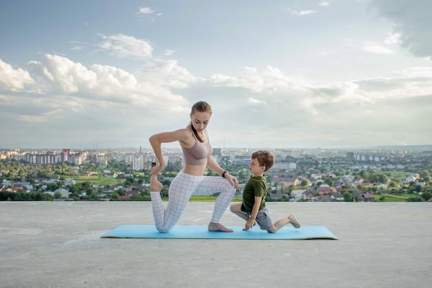 Matka i syn robi ćwiczenia na balkonie w tle miasta podczas wschodu lub zachodu słońca, koncepcja zdrowego stylu życia.