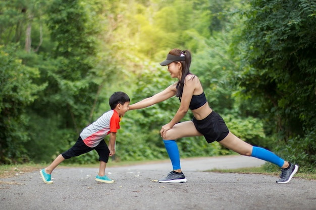 Matka i syn robią ćwiczenia. rodzina robi fitness w parku. zdrowe pojęcie rodziny