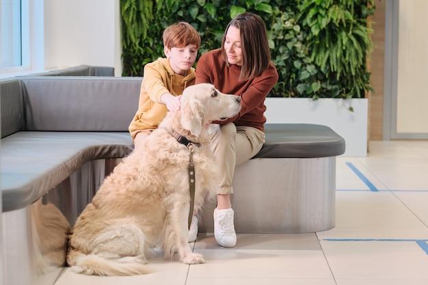 Matka i syn siedzą na kanapie z psem i czekają na wizytę u weterynarza w przychodni