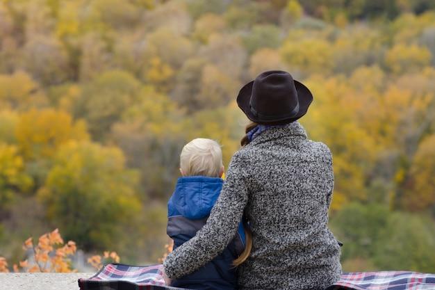 Matka i syn siedzą na wysokim terenie. jesień. las w oddali. widok z tyłu