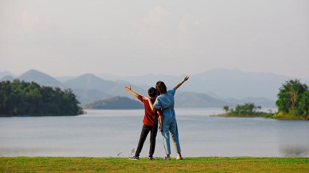 Matka i syn stojący nad dużym jeziorem, aw tle widok na góry. pomysł na wspólne wyjazdy turysty rodzinnego na wycieczkę w plenerze.