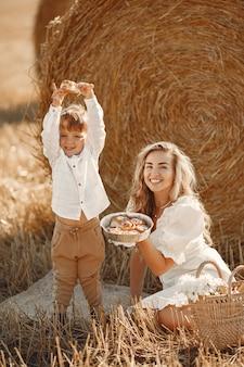 Matka i syn. stos siana lub beli na żółtym polu pszenicy w lecie. dzieci bawią się razem.