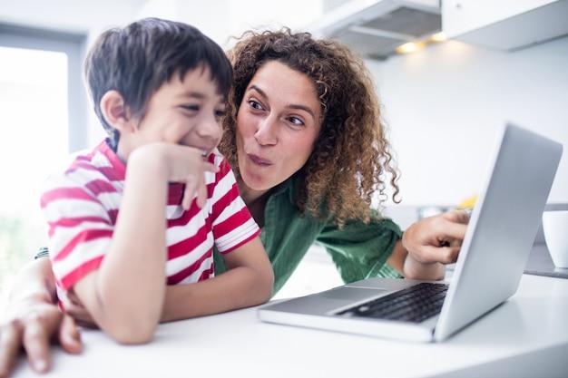 Matka i syn używa laptop w kuchni