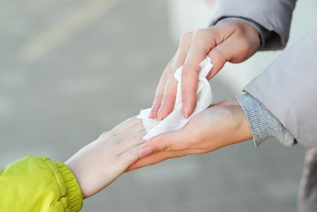 Matka i syn używają sprayu dezynfekującego do rąk na zewnątrz, aby zapobiec rozprzestrzenianiu się zarazków, bakterii, koronawirusa i wirusa.