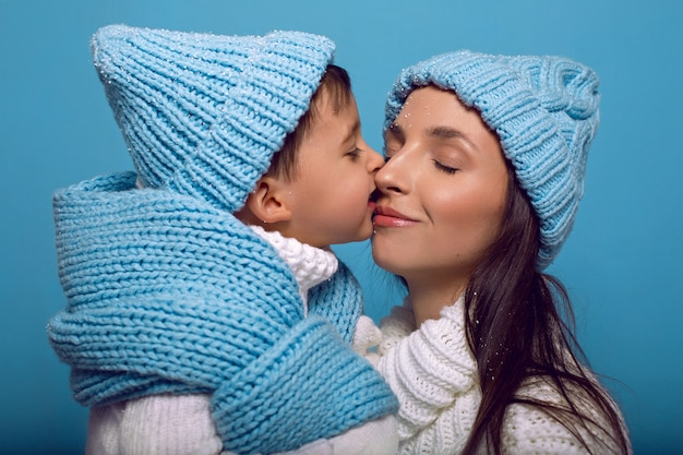 Matka i syn w białych swetrach i niebieskich czapkach stoją na niebiesko w studio