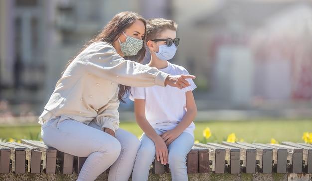 Matka i syn w maskach na twarz siedzą na miejskiej ławce, a ona wskazuje kierunek, w którym patrzą oboje.