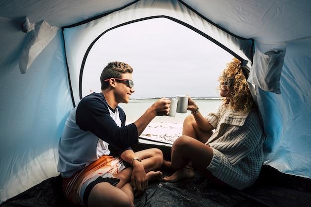 Matka i syn w rodzinnych zajęciach rekreacyjnych na świeżym powietrzu i ciesz się kempingiem na plaży w pobliżu morza i czując fale, pijąc filiżankę herbaty lub kawy i żyj szczęśliwie