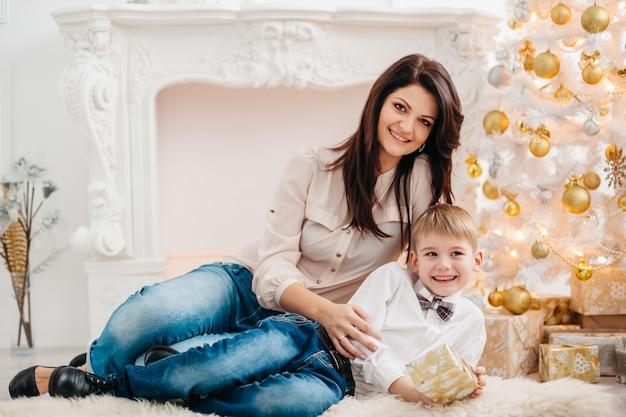 Matka i syn w studio boże narodzenie. portret szczęśliwa matka i synek siedzi w pobliżu choinki.